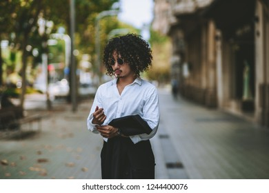 A curly Asian guy in sunglasses is belting the sleeve of his white shirt and holding a blazer from his formal suit in the hands while standing in the center of a sidewalk in Barcelona, Spain