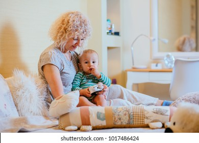 Curly blond caucazian grandmother with her grandson sitting on bedroom and playing with alarm clock. in cozy home interior. Real people life and different generations concept.