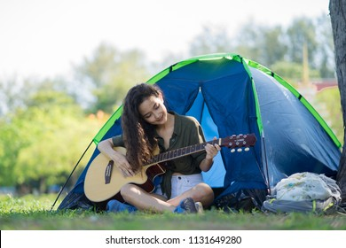 Curly blond long hair asian teenager girl with long shrit and white shorts, playing guitar front of blue canvas camping tent on grass field with smile happy face