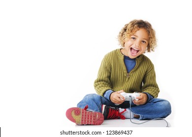 Curly blonde 5 year old boy sitting smiling with game controls on white background