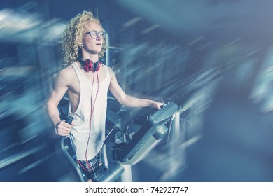 Curly blonde man with glasses trains on a treadmill. Toned