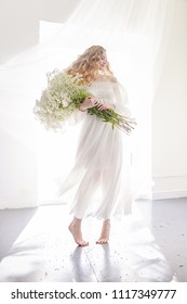 Curly blonde romantic look, beautiful eyes. White wildflowers in hands. Girl white light dress and curly hair, portrait of woman with flowers at home near the window, purity and innocence