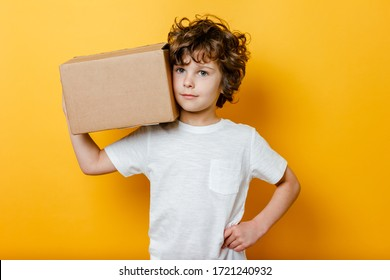 Curly Boy holds a cardboard box on his shoulder on yellow background. Concept of Food delivery, shopping online service.