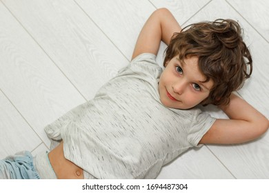 Curly boy lying on white floor at home and smiling. The concept of underfloor heating, quality laminate