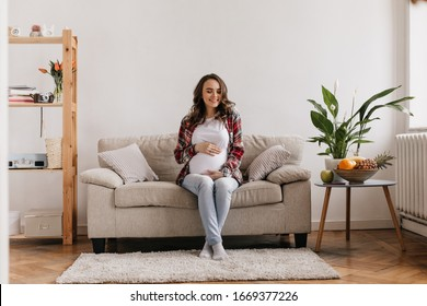 Curly brunette pregnant woman gently smiles and touches belly. Cute lady in plaid shirt, denim pants and white tee resting on beige sofa in cozy living room