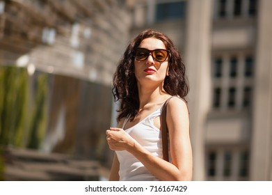 Curly brunette in sunglasses. Arrogant and confident look. Portrait, Prague, May 28, 2017, near the monument to Hlava Franze Kafka. - Shutterstock ID 716167429