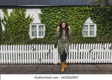 Curly brunette woman in khaki jacket and orange boots sitting on white fence of house with small white windows and wall, covered with green ivy plant. Trendy autumn look.