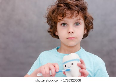 Curly child boy brushes big toy teeth on gray background. Concept of oral hygiene.
