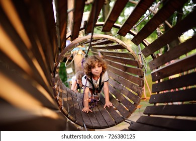 a curly child in climbing safety equipment in a tree house or in a rope park climbs the rope. Active children
