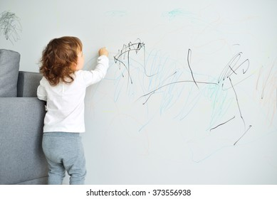Curly cute little baby girl drawing with crayon color on the wall. Works of child - Shutterstock ID 373556938