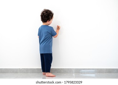 Curly cute little toddler boy painting with color pencil on the wall.