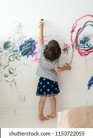 Curly cute little toddler girl painting with paints color and brush on the wall. Works of child