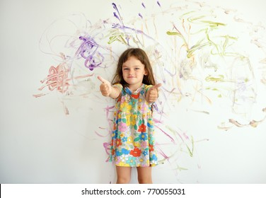Curly cute little toddler girl finished painting with paints color and brush on the wall. Works of child. Thumbs up.