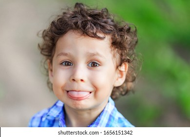 curly dark-haired boy in the summer depicts different emotions, close-up