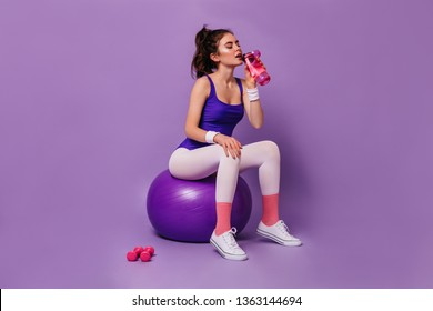 Curly dark-haired girl in sportswear in style of 80s sits on fitball and drinks water from pink bottle