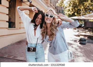 Curly debonair girl dancing with friend on the street. Outdoor photo of latin brunette woman having fun with sister.