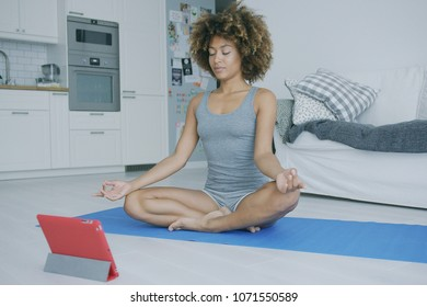 Curly fit model in shorts and top sitting on mat at home meditating with eyes closed and breathing while trainin yoga with tablet in front.