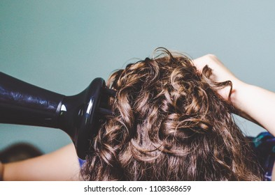 curly girl with a hairdryer