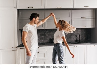 Curly girl in jeans chilling with boyfriend at home. Indoor shot of carefree couple dancing in kitchen.