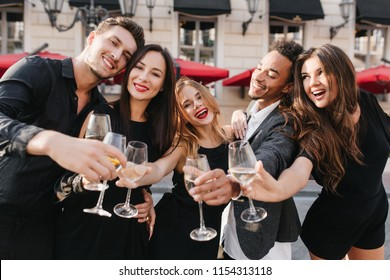 Curly girl with light-brown hair standing with african man in jacket and looking away with smile. Outdoor photo of ecstatic friends celebrating graduation with champagne.