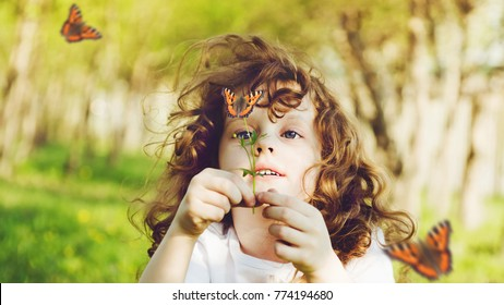 Curly girl looking at a butterfly on wild flower. The child explores the nature.