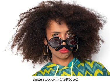 curly girl posing in the Studio on an isolated background. the girl is joking and fooling around. a dark-skinned girl jokes with a cardboard mustache in her face.