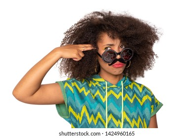 curly girl posing in the Studio on an isolated background. the girl is joking and fooling around. a dark-skinned girl jokes with a cardboard mustache in her face. the girl keeps a hand near his temple