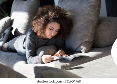 curly girl reading some magazine or catalogue on a big sofa in her living room