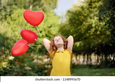 Curly girl with red heart balloons resting in a summer park. Happy childhood and medical, healthy lifestyle concept.