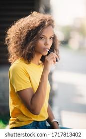 Curly girl smoking electric cigarette. Beautiful young girl smoking.