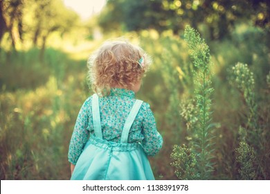 Curly girl standing with her back in the garden. Sweet and funny baby girl, cute toddler two years old.