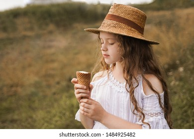 Curly girl in a straw hat eats ice cream in the village in the summer.Retro vintage, happy childhood concept.