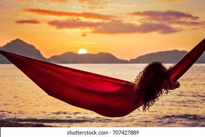 Curly girl swinging in a hammock enjoying the sunset on a tropical island