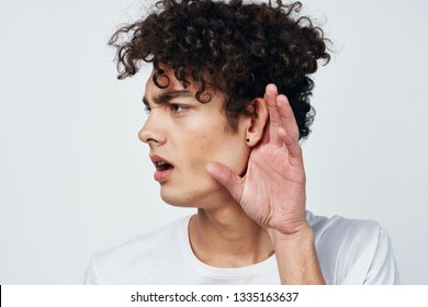 curly guy touches his ear to eavesdrop on a conversation