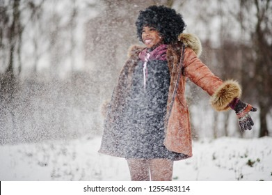 Curly hair african american woman wear on sheepskin coat and gloves posed at winter day throws up snow, blured focus.