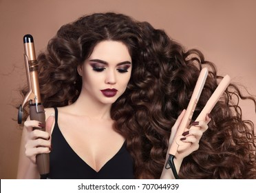 Curly hair. Beauty Close-up of brunette girl with blowing hairstyle holding curling and straightening iron. Marsala eye shadow makeup. Glamour fashionable female isolated on beige background.