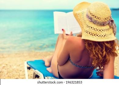 Curly hair female reading a book on the beach.
