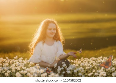 Curly hair girl with a butterfly on his hand on meadow outdoors. Health and medical, happy childhood concept.