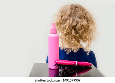 Curly hair girl child with curly hair spray balm and brush to help combing messy fuzzy hair concept. Indoors minimal white background.