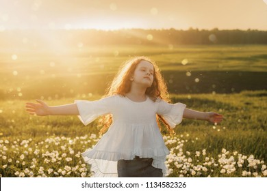 Curly hair girl closed her eyes and breathing with fresh blowing air on meadow outdoors. Health and medical concept.