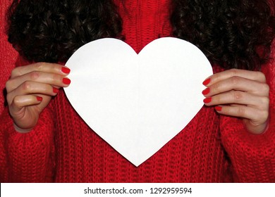 Curly hair girl in red sweater holds white heart with space for text. Valentines Day concept