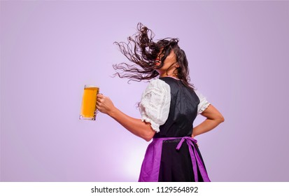 Curly hair girl , throwing hair and holding beer mug ; Oktoberfest, studio shot