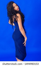 Curly hair girl wearing blue dress studio shot