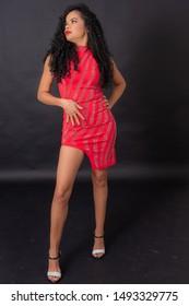 Curly hair girl wearing red dress studio shot