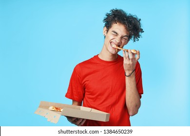 curly hair guy eating a slice of pizza and holding a paper box in his hand