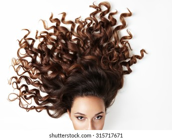 curly hair and part of woman'?s face, looking at the camera