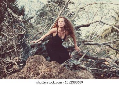 Curly hair woman in a black dress on the nature in the forest