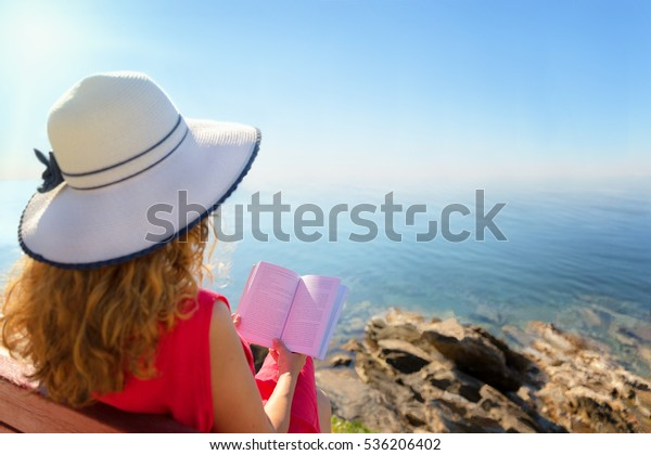 Curly hair woman reading a book against sea horizon.