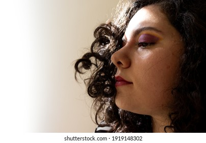 Curly hair woman in the wind. Woman with stylish makeup on. Curls flowing with the wind  into a woman's face. Curly hair blowing in the wind. Purple and yellow makeup.