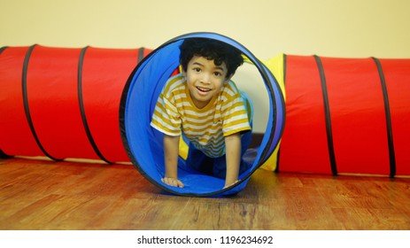 Curly hair young Asian boy play with playground tunnel